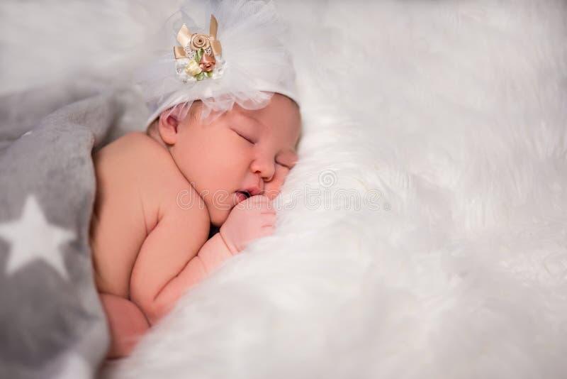 Fermez-vous vers le haut du portrait du bébé nouveau-né de sommeil mignon dans le beau chapeau images stock