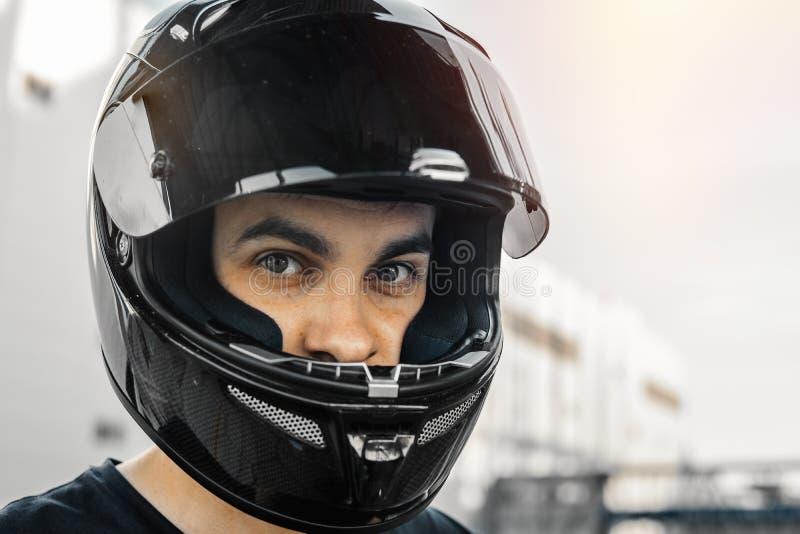 Fermez-vous vers le haut du portrait du cycliste dans le casque brillant noir sur le fond urbain photographie stock libre de droits