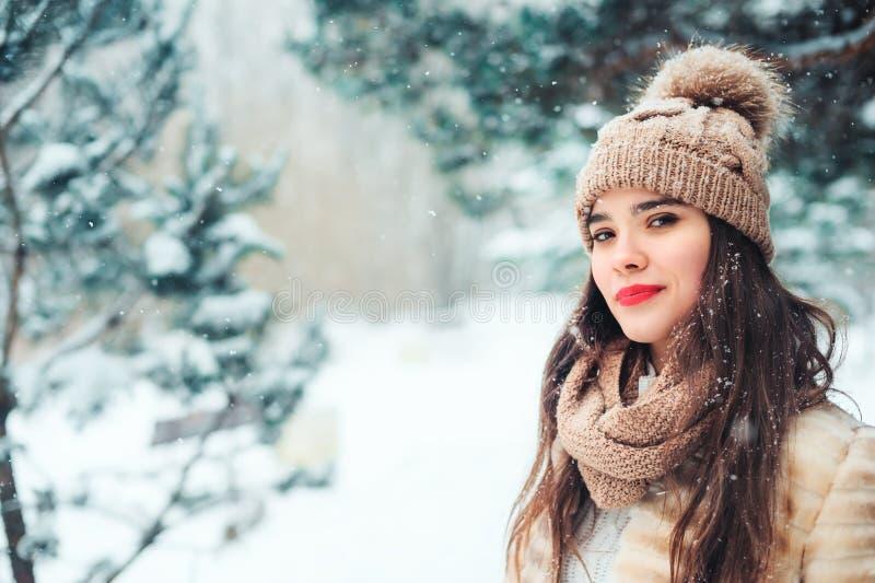 fermez-vous vers le haut du portrait d'hiver de la jeune femme de sourire marchant dans la forêt neigeuse photos libres de droits