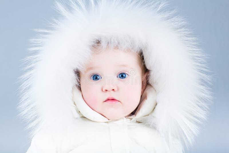 Fermez-vous vers le haut du portrait d'un beau bébé dans la veste d'hiver photos stock