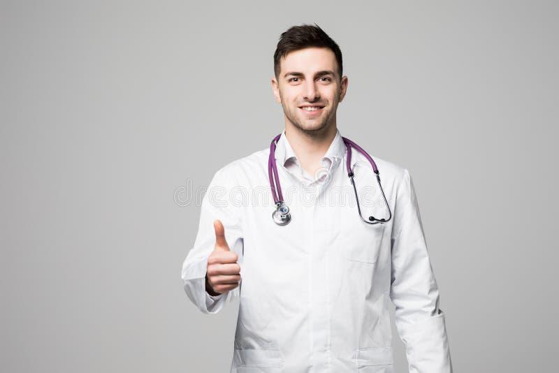 Fermez-vous vers le haut du portrait d'un docteur masculin gai de sourire avec le stéthoscope montrant des pouces d'isolement sur photo stock