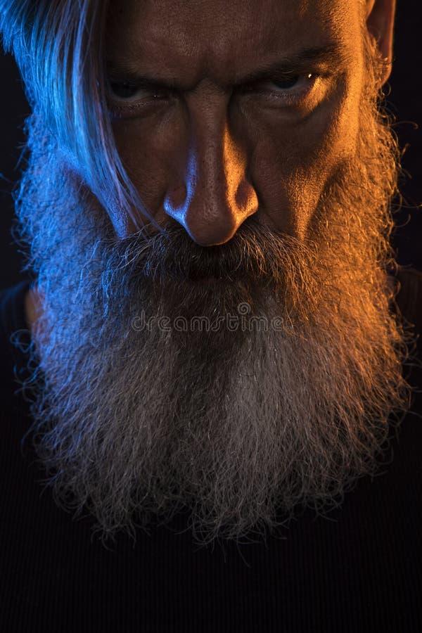 Fermez-vous vers le haut du portrait d'un homme barbu fâché avec la lumière orange et bleue images stock