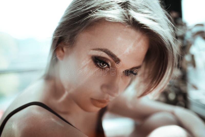 Fermez-vous vers le haut du portrait d'une belle jeune femme avec les cheveux blonds Effet léger de photo de fusée La fille avec  image libre de droits