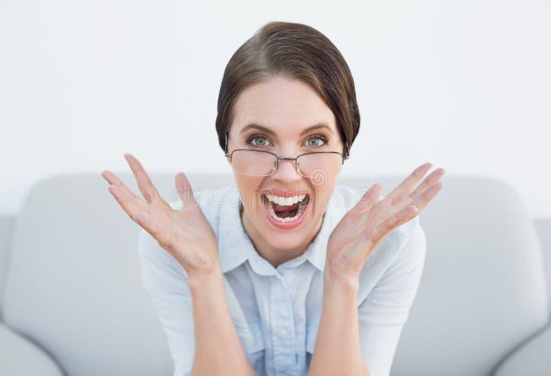 Fermez-vous vers le haut du portrait d'une femme contrariée criant sur le sofa photos libres de droits