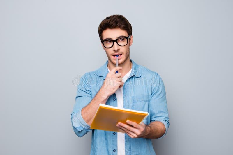 Fermez-vous vers le haut du portrait de considérer le stylo acéré de beau type intelligent attirant intelligent futé mignon adora photos libres de droits