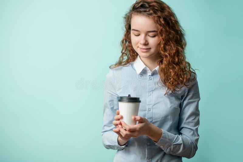 Fermez-vous vers le haut du portrait de l'ado femelle de gingembre tenant et regardant le café image stock
