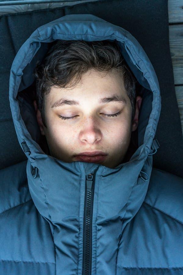 Fermez-vous vers le haut du portrait de l'adolescent de jeune homme avec la veste bleue de port de capot d'hiver fermée par yeux photos stock