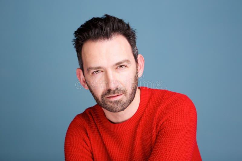 Fermez-vous vers le haut du portrait de l'homme bel avec la barbe sur le fond bleu photographie stock