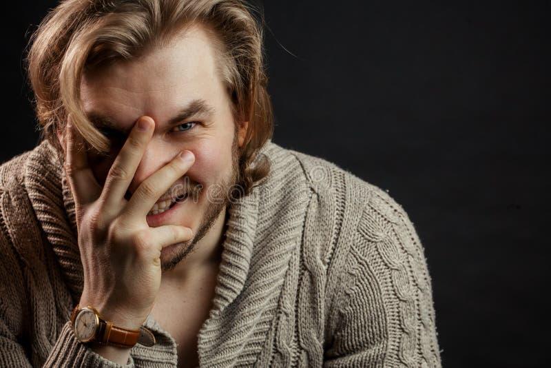 Fermez-vous vers le haut du portrait de l'homme brutal riant et fermant son visage avec la main photographie stock libre de droits