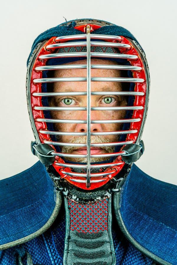 Fermez-vous vers le haut du portrait de l'homme dans le casque de kendo, studio de kendoka tiré sur le blanc images stock
