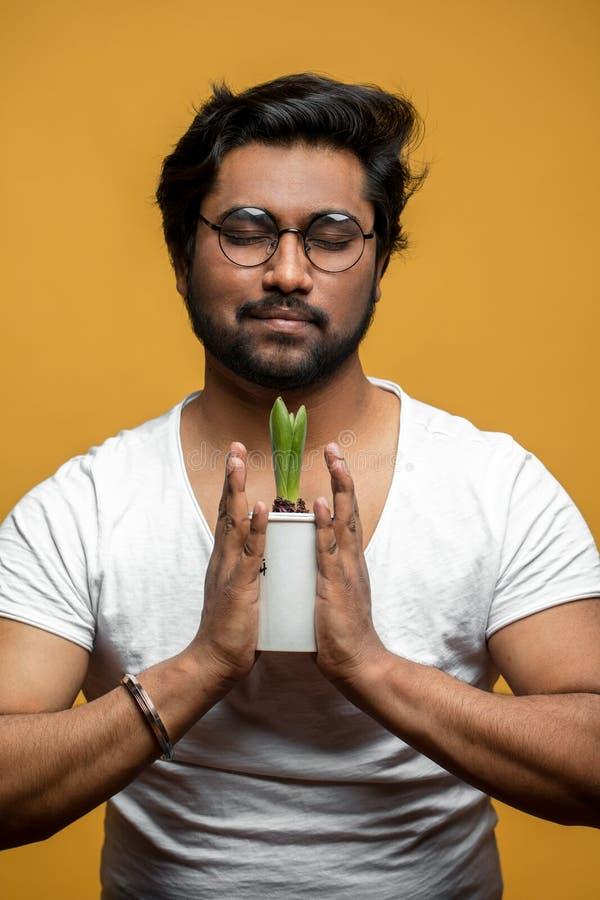 Fermez-vous vers le haut du portrait de l'homme indien priant à la croissance de la fleur image libre de droits