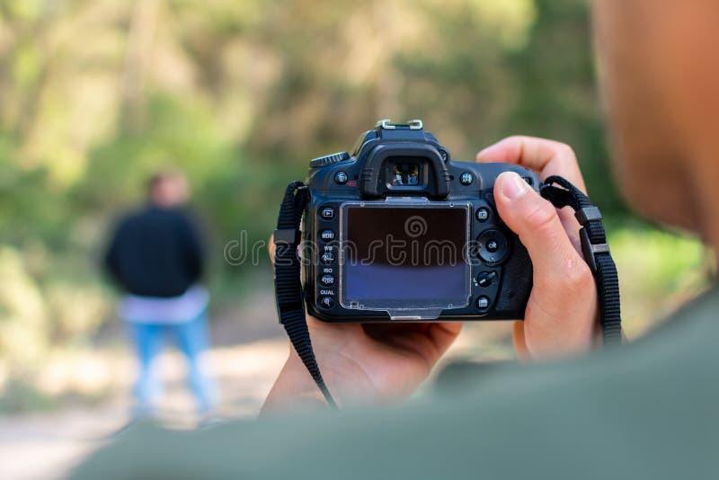 Fermez-vous vers le haut du portrait de l'homme de photographe prenant la photo avec l'appareil photo num?rique image stock