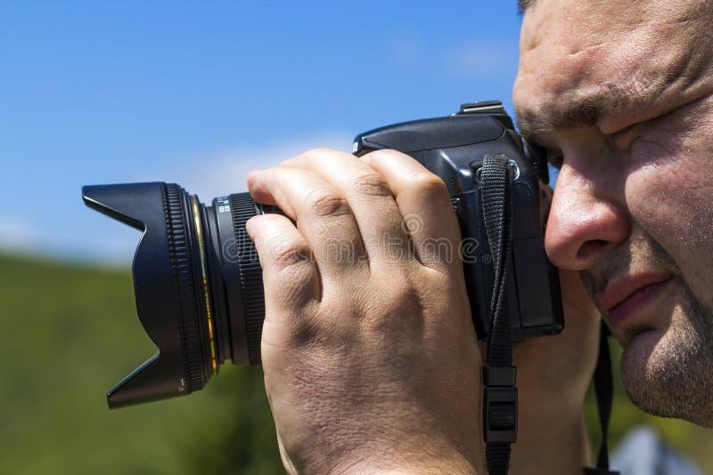 Fermez-vous vers le haut du portrait de l'homme de photographe prenant la photo avec le digita photos stock