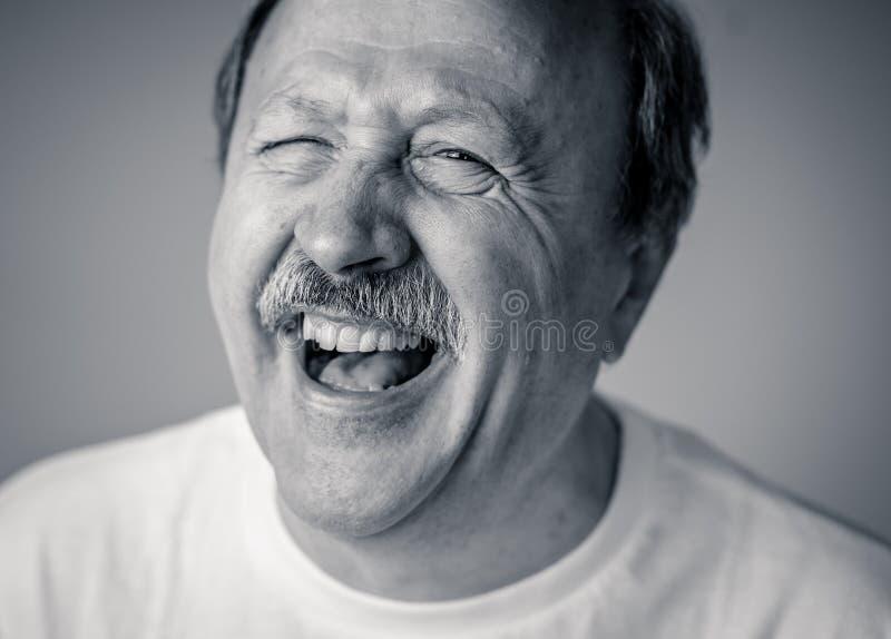 Fermez-vous vers le haut du portrait de l'homme supérieur de sourire avec le visage heureux regardant l'appareil-photo photographie stock