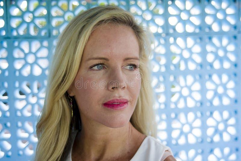 Fermez-vous vers le haut du portrait de la belle et décontractée femme blonde caucasienne avec des yeux bleus regardant loin sur  images stock