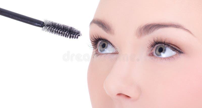 Fermez-vous vers le haut du portrait de la belle femme appliquant le mascara sur son oeil images libres de droits