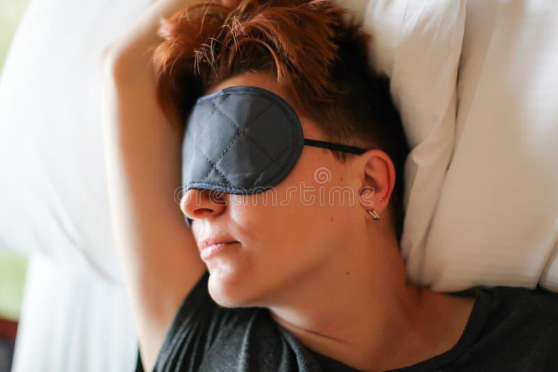 Fermez-vous vers le haut du portrait de la belle femme caucasienne adulte dormant dans le lit blanc avec le masque d'oeil gris photos libres de droits