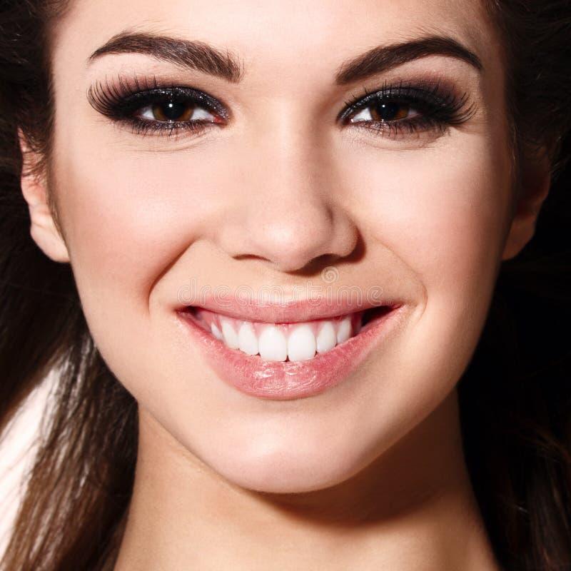 Fermez-vous vers le haut du portrait de la belle jeune femme de sourire heureuse, d'isolement au-dessus du fond blanc photographie stock libre de droits
