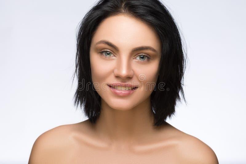 Fermez-vous vers le haut du portrait de la belle jeune femme de sourire heureuse, d'isolement au-dessus du fond blanc photos libres de droits