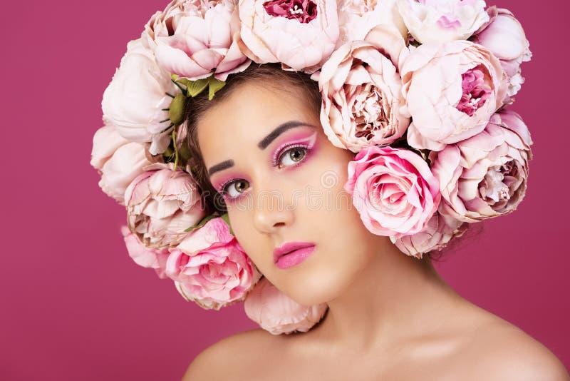 Fermez-vous vers le haut du portrait de la belle jeune fille avec les roses roses fleurissent sur la tête et composent image libre de droits