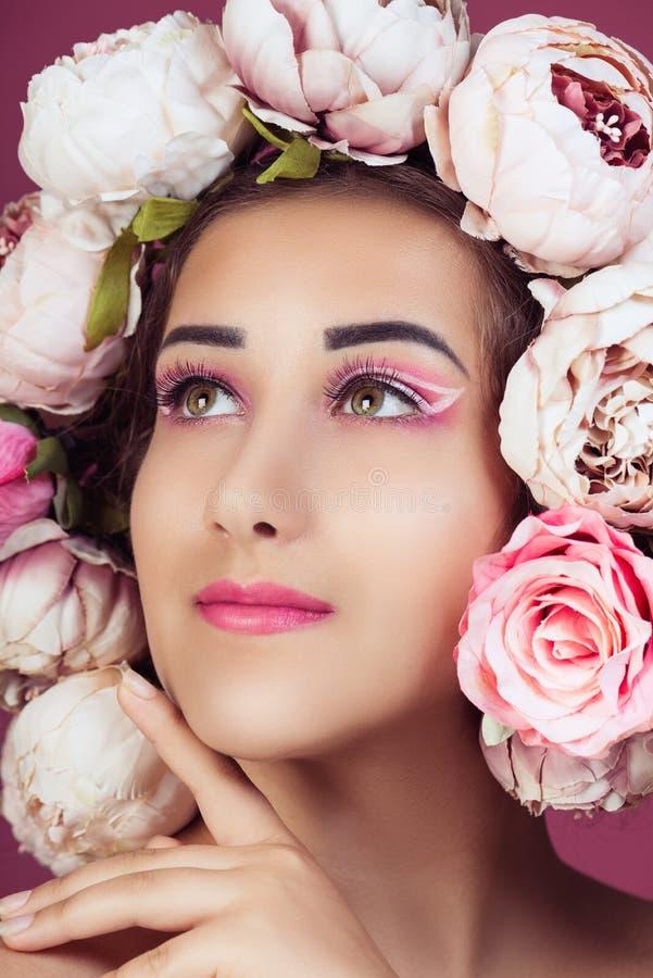 Fermez-vous vers le haut du portrait de la belle jeune fille avec les roses roses fleurissent sur la tête et composent photos libres de droits