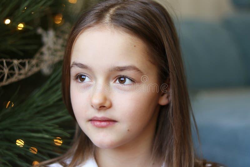 Fermez-vous vers le haut du portrait de la belle petite fille avec les yeux bruns se reposant sous l'arbre de Noël rêvassant photographie stock