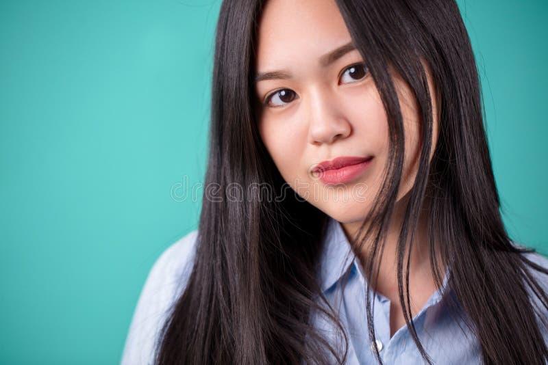Fermez-vous vers le haut du portrait de la femme asiatique de longs cheveux avec la chemise blanche photo libre de droits