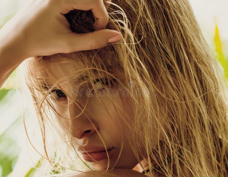 Fermez-vous vers le haut du portrait de la femme blonde avec les cheveux humides sur t ensoleillé vert photos libres de droits