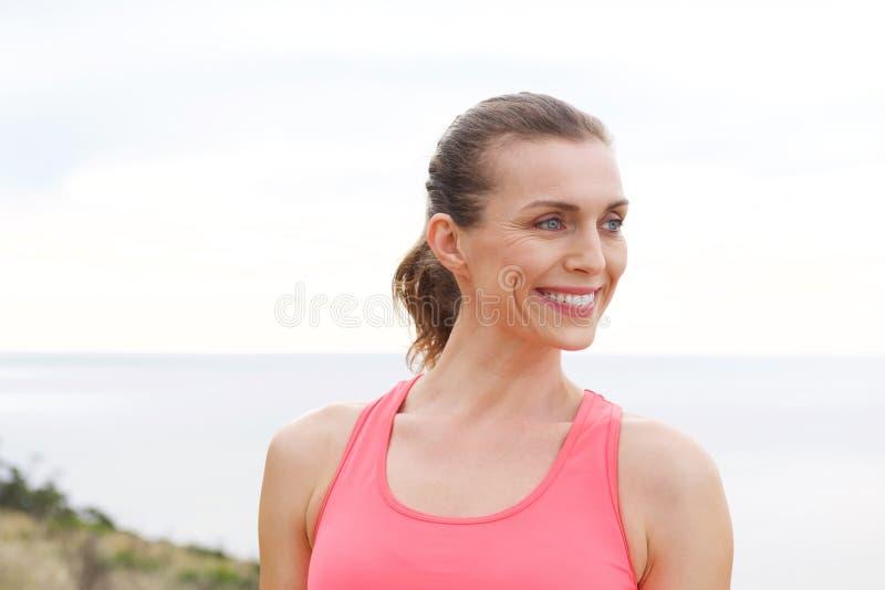 Fermez-vous vers le haut du portrait de la femme de sport souriant dehors image libre de droits