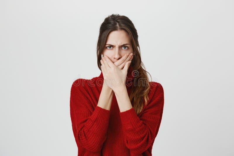 Fermez-vous vers le haut du portrait de la femme européenne effrayée par renversement, couvrant la bouche des deux mains pour emp photo stock