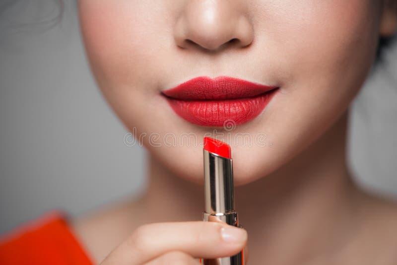 Fermez-vous vers le haut du portrait de la fille attirante tenant le rouge à lèvres rouge au-dessus de g photo libre de droits