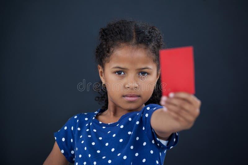 Fermez-vous vers le haut du portrait de la fille montrant la carte rouge photo libre de droits