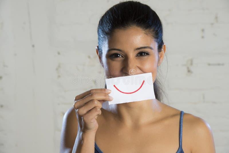 Fermez-vous vers le haut du portrait de la jeune belle et heureuse femme hispanique souriant avec le papier dans la bouche photographie stock libre de droits