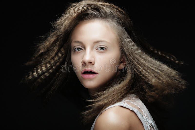 Fermez-vous vers le haut du portrait de la jeune femme blonde avec les cheveux bouclés au-dessus du fond noir photographie stock