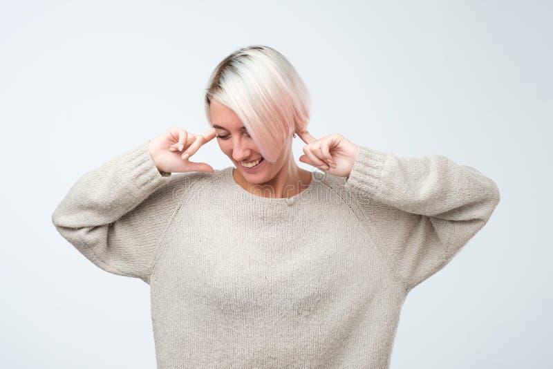 Fermez-vous vers le haut du portrait de la jeune femme branchant des oreilles avec des doigts photographie stock libre de droits