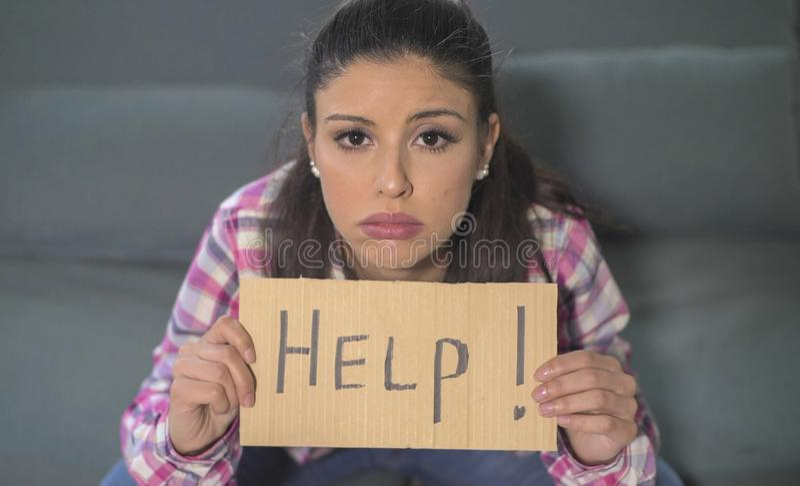 Fermez-vous vers le haut du portrait de la jeune femme hispanique attirante et triste reposant à la maison le divan semblant sign photographie stock libre de droits