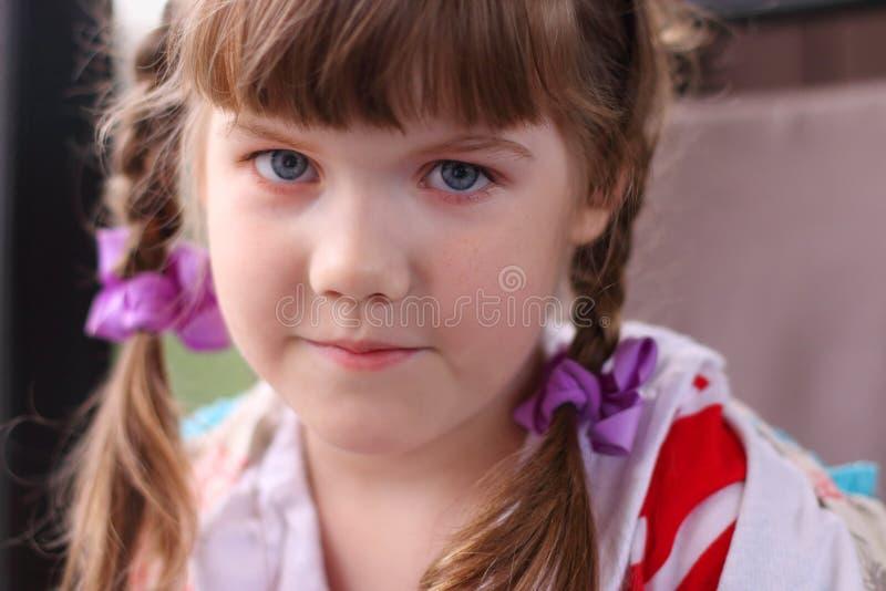 Fermez-vous vers le haut du portrait de la petite fille assez de sourire avec des tresses avec photo stock