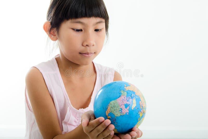 Fermez-vous vers le haut du portrait de la petite fille mignonne tenant la terre photo libre de droits