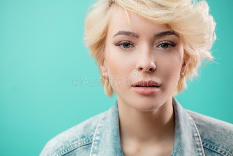 Fermez-vous vers le haut du portrait de la veste de port de denim de mode de belle femme blonde images stock