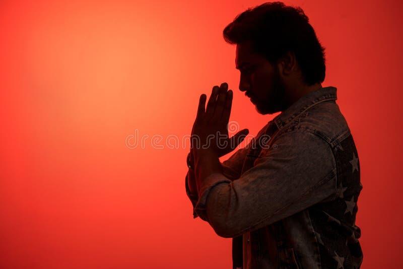 Fermez-vous vers le haut du portrait de vue de côté du type indien faisant le coucher du soleil de yoga photographie stock libre de droits