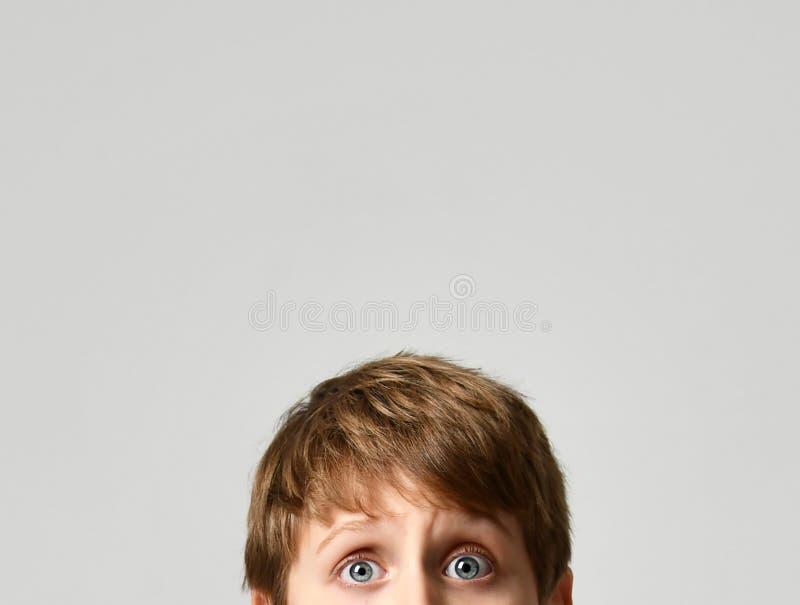 Fermez-vous vers le haut du portrait des yeux d'écolier regardant sur le gris photographie stock