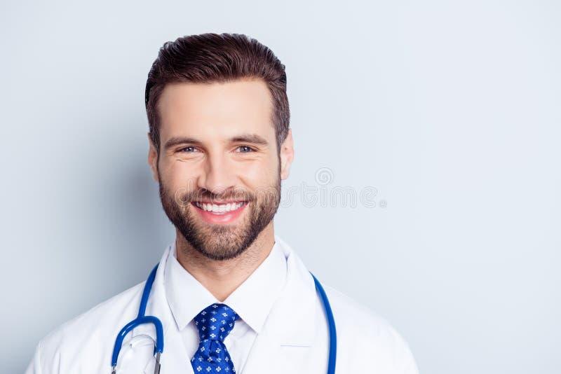 Fermez-vous vers le haut du portrait du docteur de sourire heureux dans l'uniforme d'isolement dessus photos stock