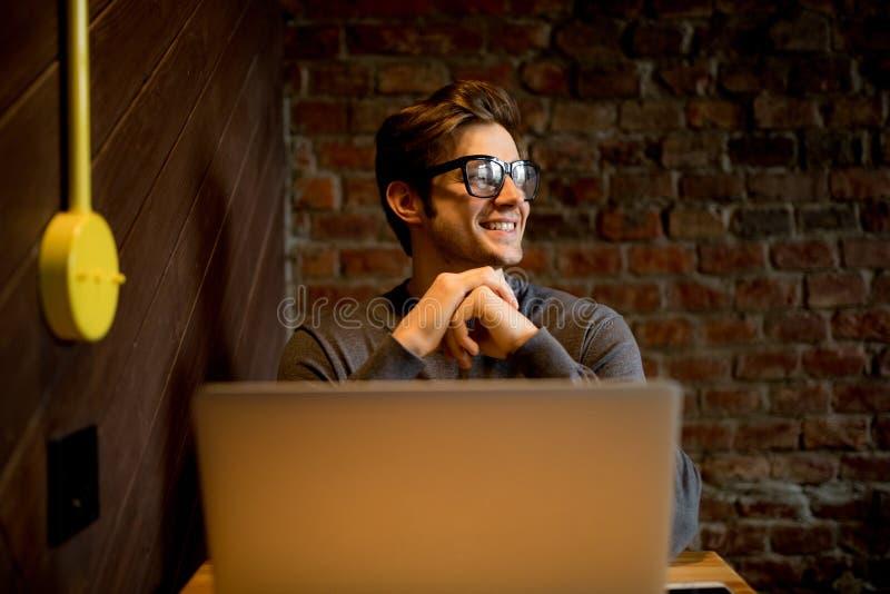Fermez-vous vers le haut du portrait du blogger masculin dans l'eyewear observant dans le windowac photographie stock libre de droits