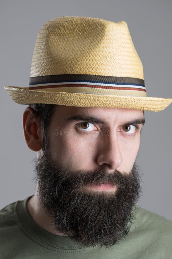Fermez-vous vers le haut du portrait du chapeau de paille de port d'homme barbu avec le regard intense à l'appareil-photo photos stock