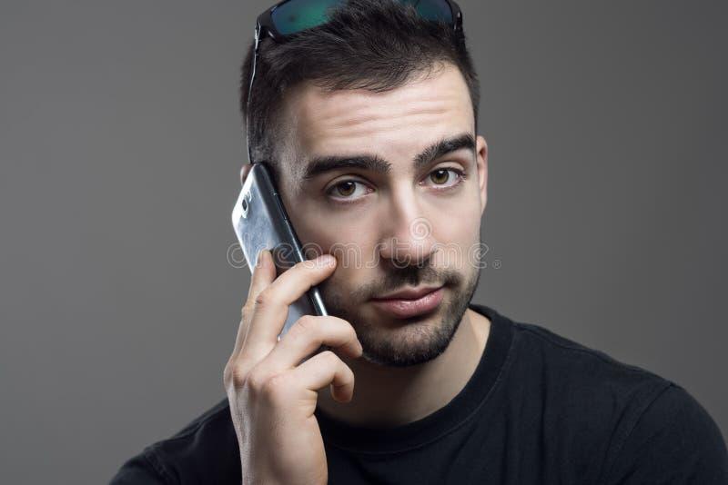 Fermez-vous vers le haut du portrait du jeune homme barbu bel dans la chemise noire parlant sur le regard de téléphone images stock