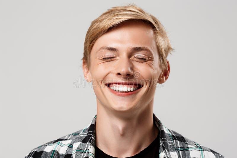Fermez-vous vers le haut du portrait du jeune homme blond beau utilisant la chemise de plaid occasionnelle souriant avec des yeux image libre de droits