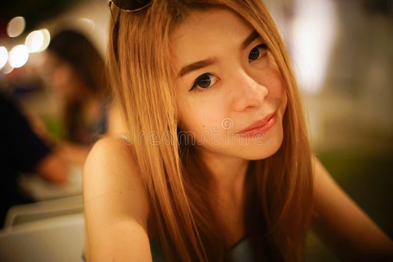 Fermez-vous vers le haut du portrait du jeune sourire asiatique et de regarder de femme l'appareil-photo avec le fond brouillé, f photographie stock libre de droits