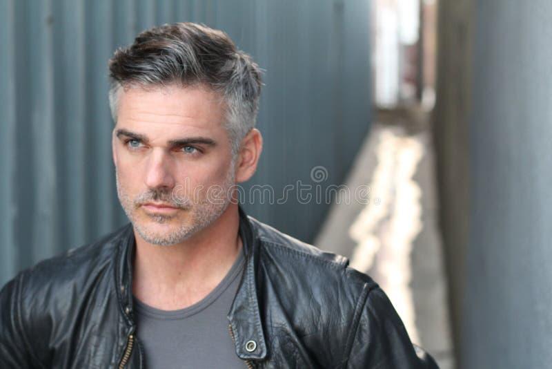 Fermez-vous vers le haut du portrait du mâle barbu d'une chevelure gris habillé dans une veste en cuir noire regardant loin photo stock