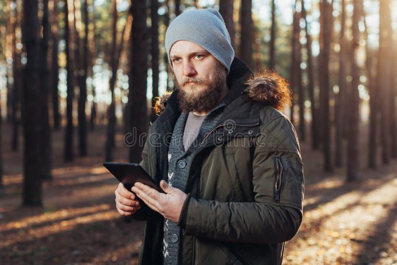 Fermez-vous vers le haut du portrait du randonneur de mâle adulte employant l'étiquette numérique et en recherchant l'emplacement images libres de droits