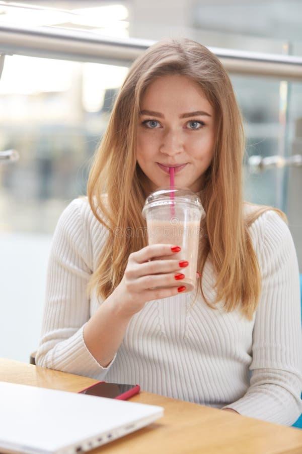 Fermez-vous vers le haut du portrait vertical de la belle fille de youn porte en passant, se repose en restaurant ou café, buvant photo stock